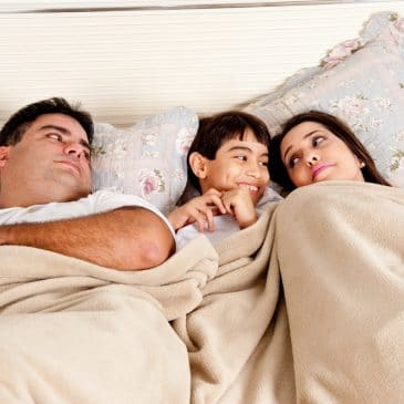 couple in bed with happy kid