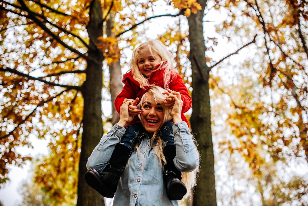 mother and kid play outside fall
