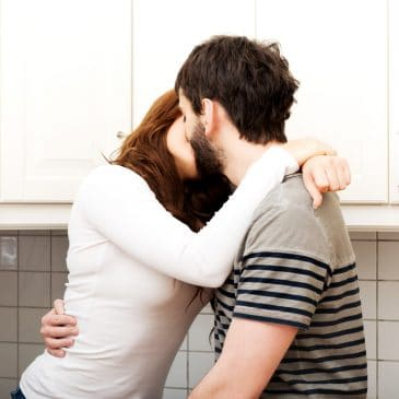 couple kissing in kitche