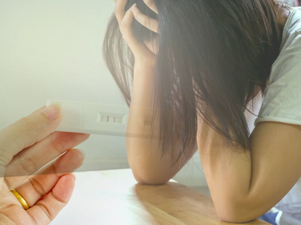 unhappy woman with pregnancy test