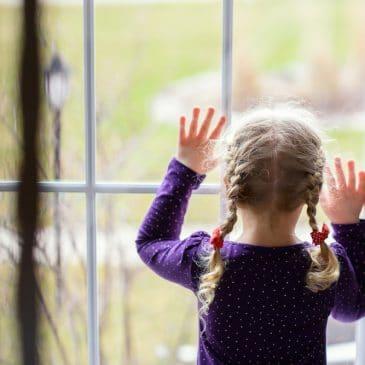 sad little girl watching window