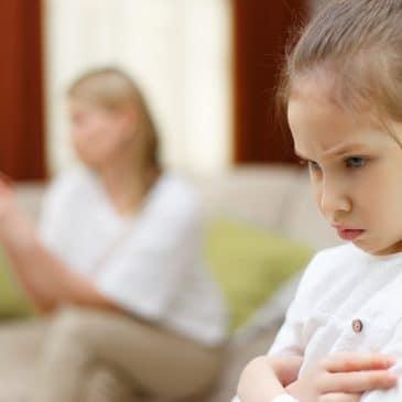 mother on phone sad little girl