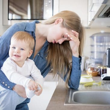 depressed mother in kitchen with babyb