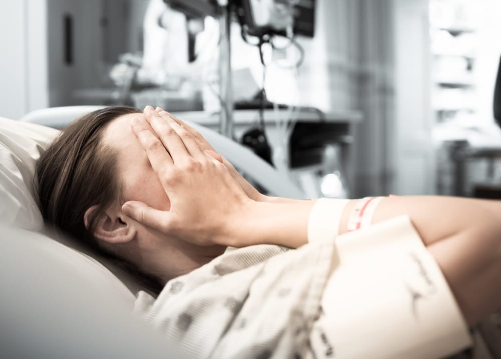 woman in hospital bed crying