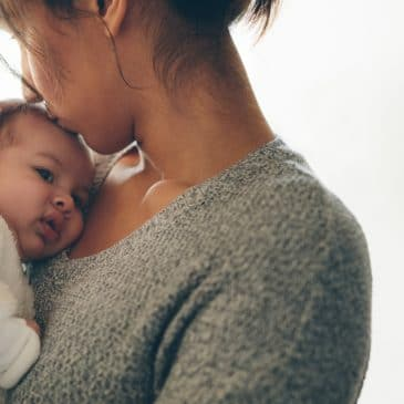 mother kiss baby head