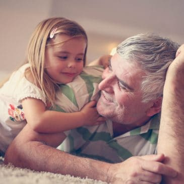 little girl and grandfather on living room