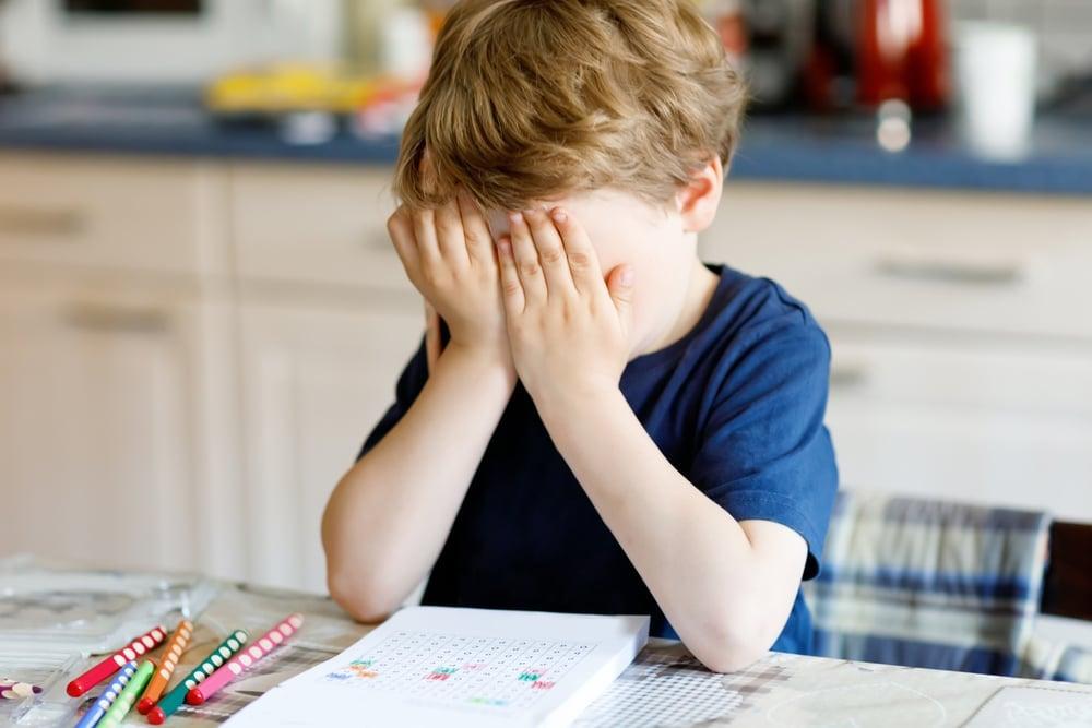 depressed young boy doing homeworks