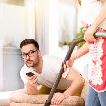 man watching tv woman vacuuming