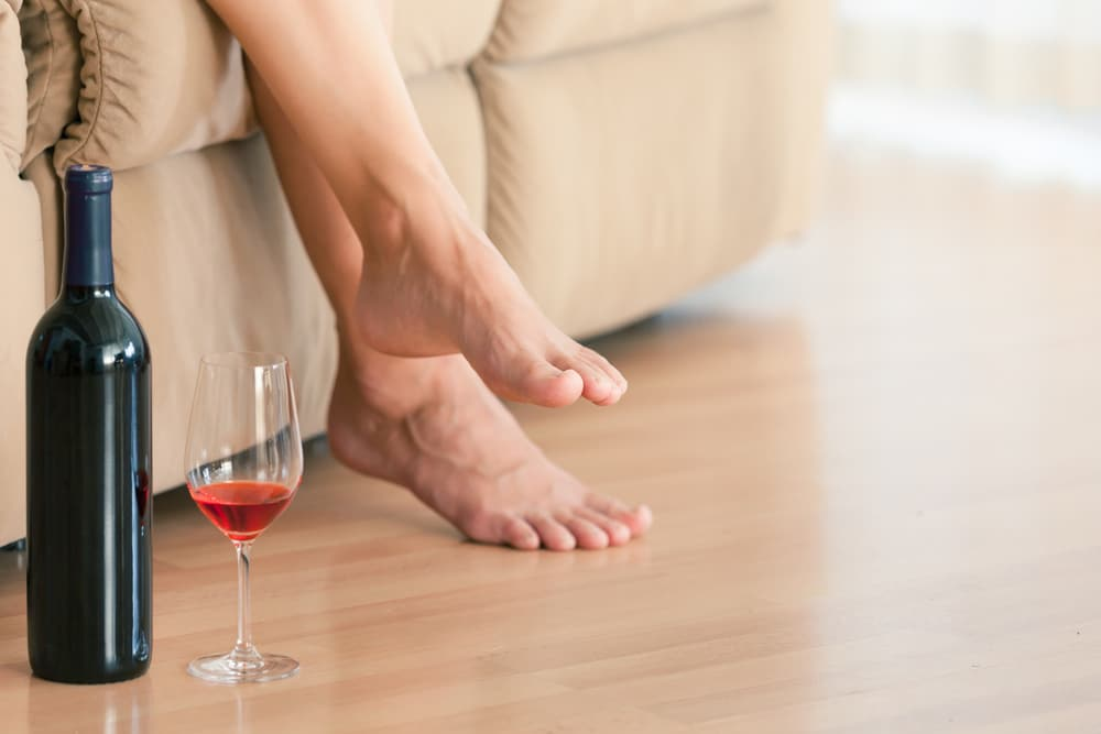 woman's feet with glass of wine
