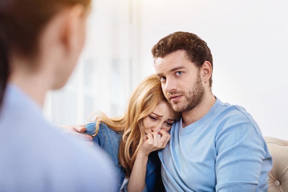 sad woman with husband and doctor
