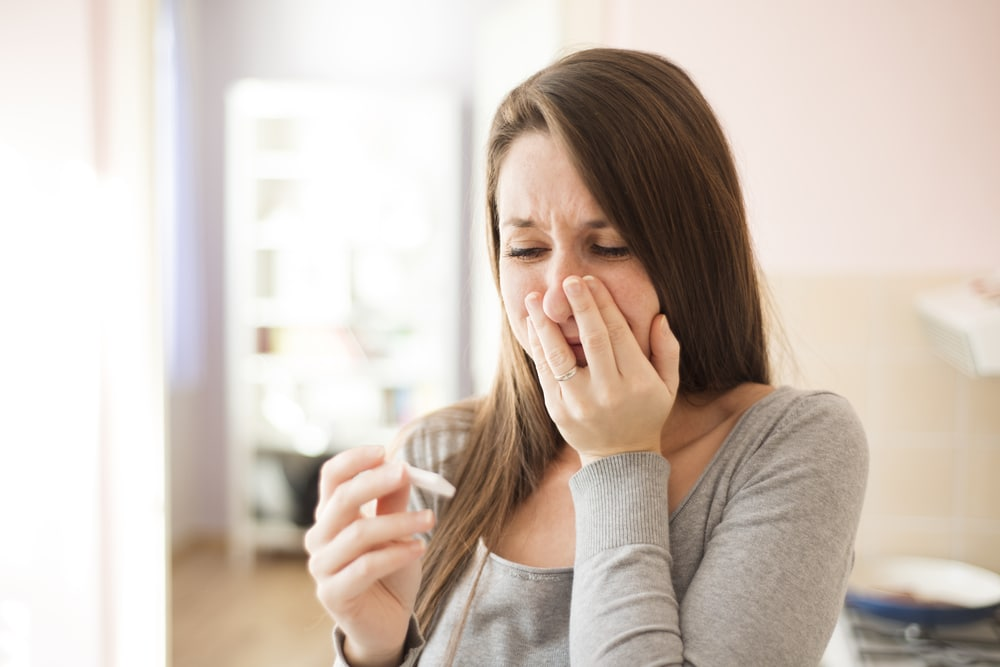 woman with pregnancy test crying