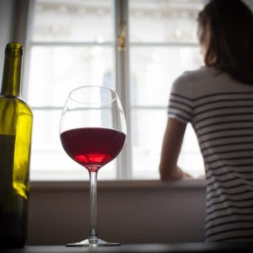 woman looking at window drinking wine
