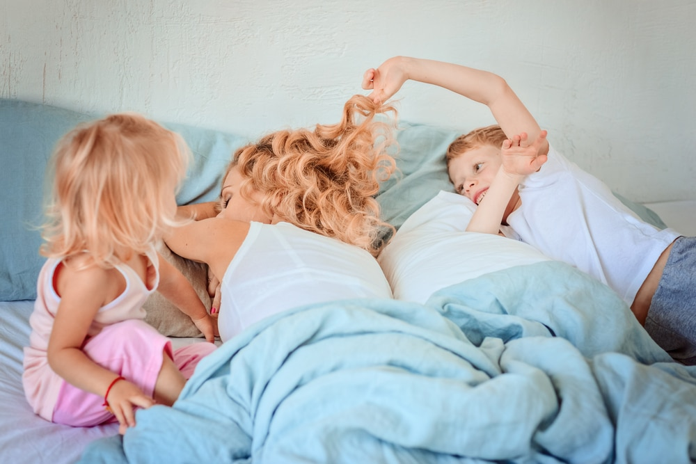 kids pulling air of mother in bed