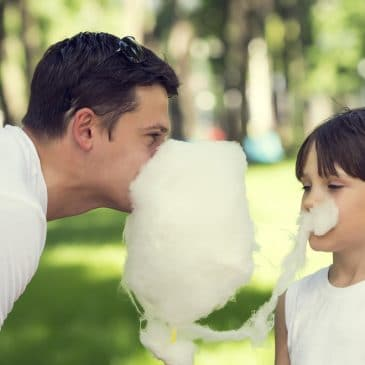 father eating cotton candy with boy