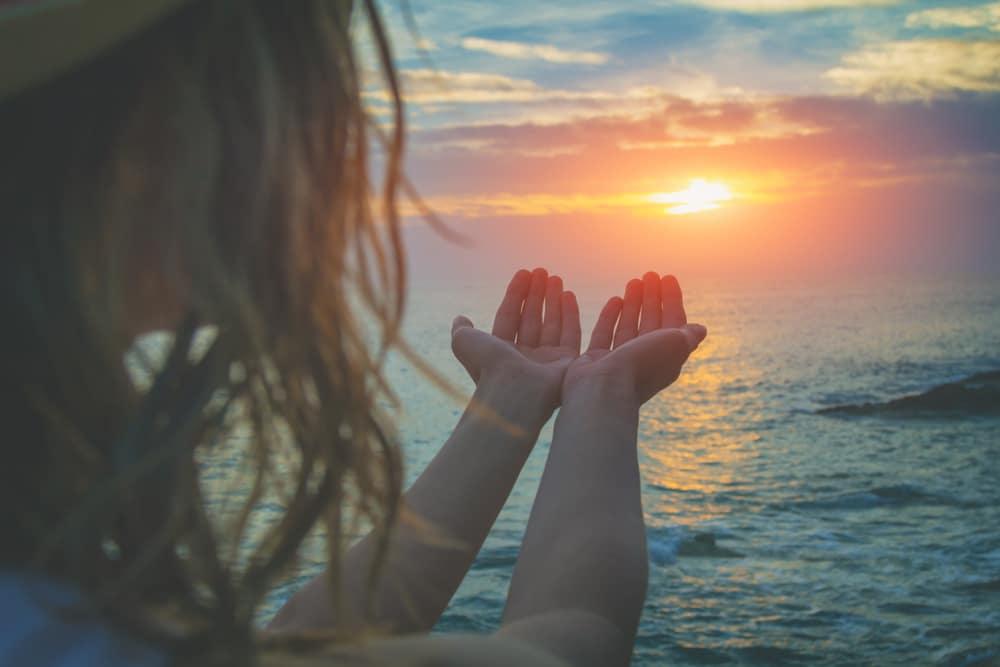 woman sea hand sun