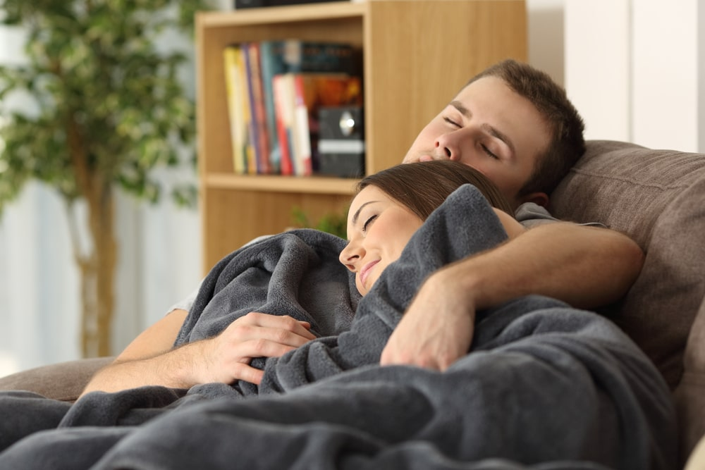 couple sleeping in couch