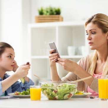 mother on cellphone with kid