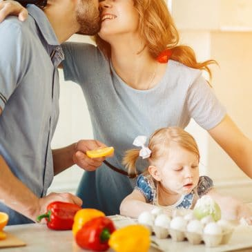 couple kissing with little girl on kitchen