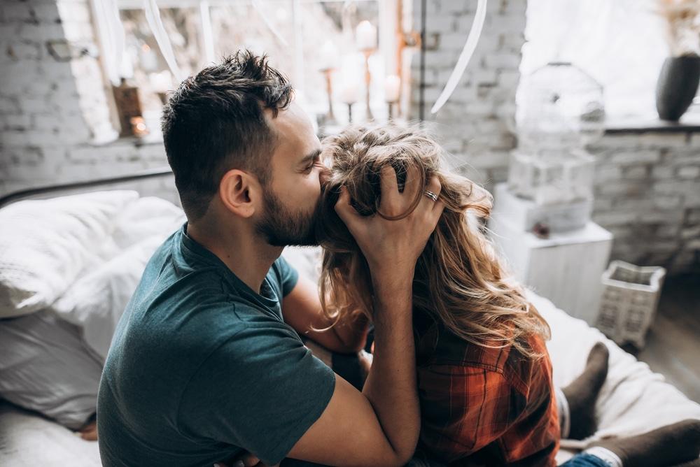 man kiss woman head