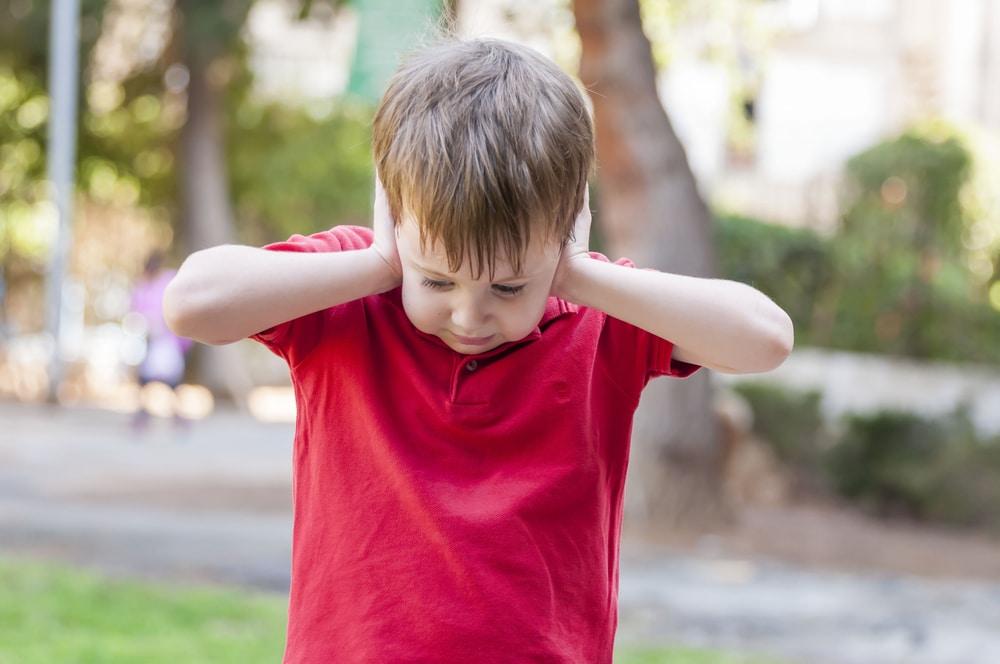 little boy close his ears