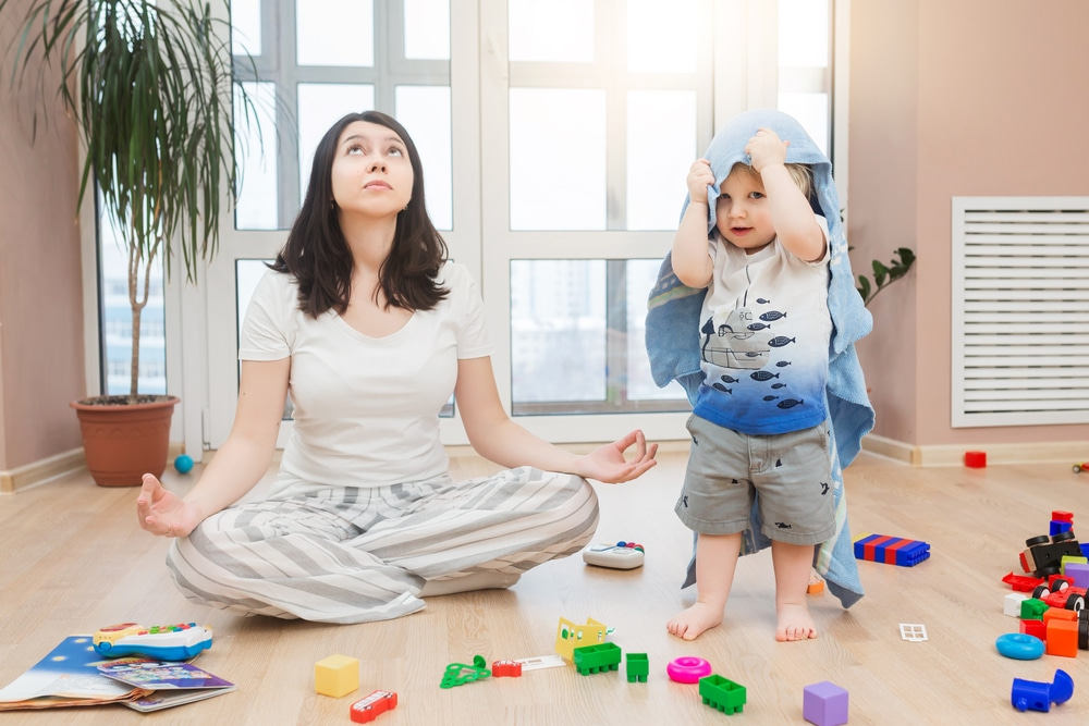 tired mother doing meditation with kid