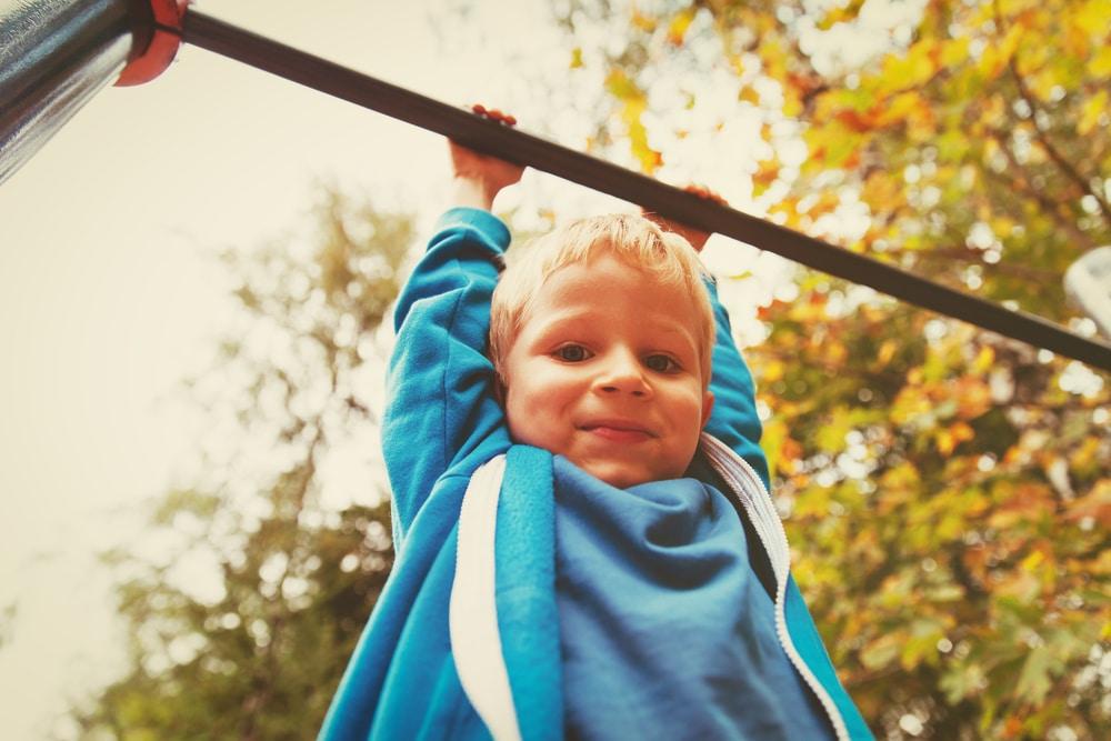 little boy on monkey bars