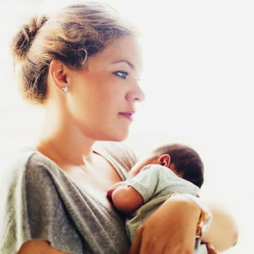 pensive woman with newborn