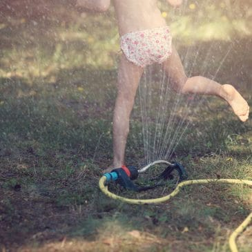 kid play with hose outside