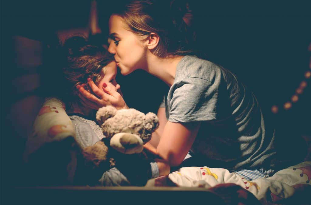 mother kiss kid at night