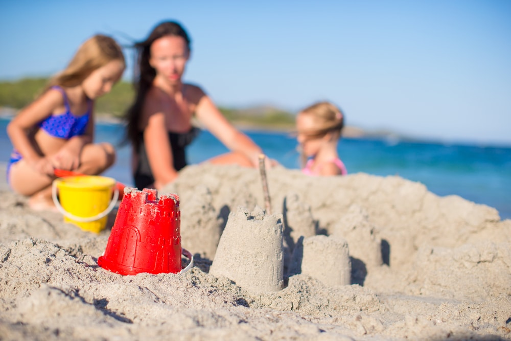 mother play with kids in the sand