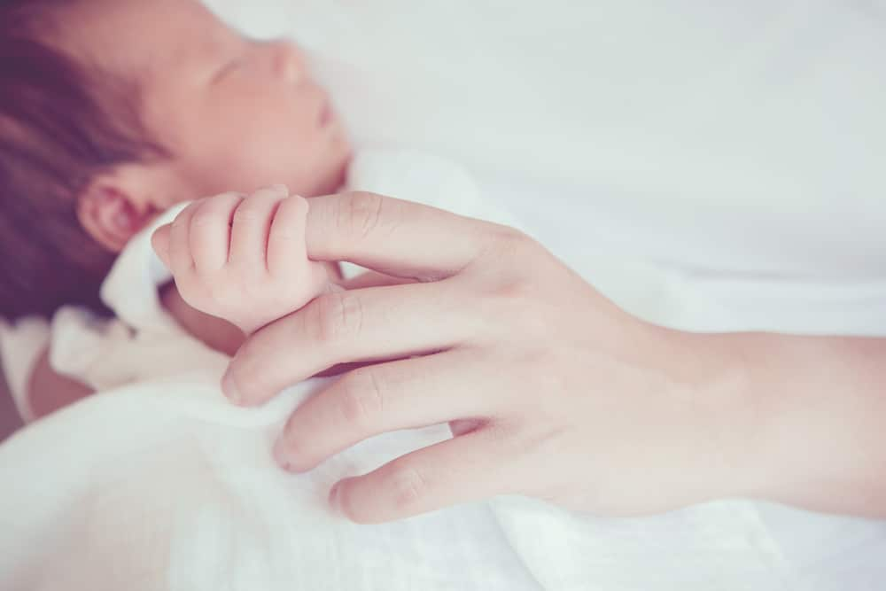 newborn with mother's finger