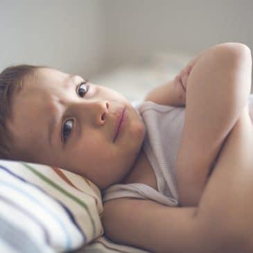 unhappy boy in bed