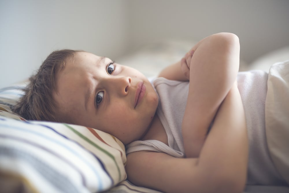 unhappy boy in bed