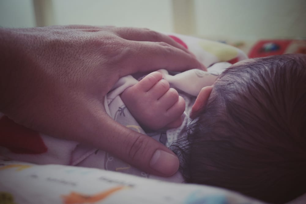 newborn with mother's hand