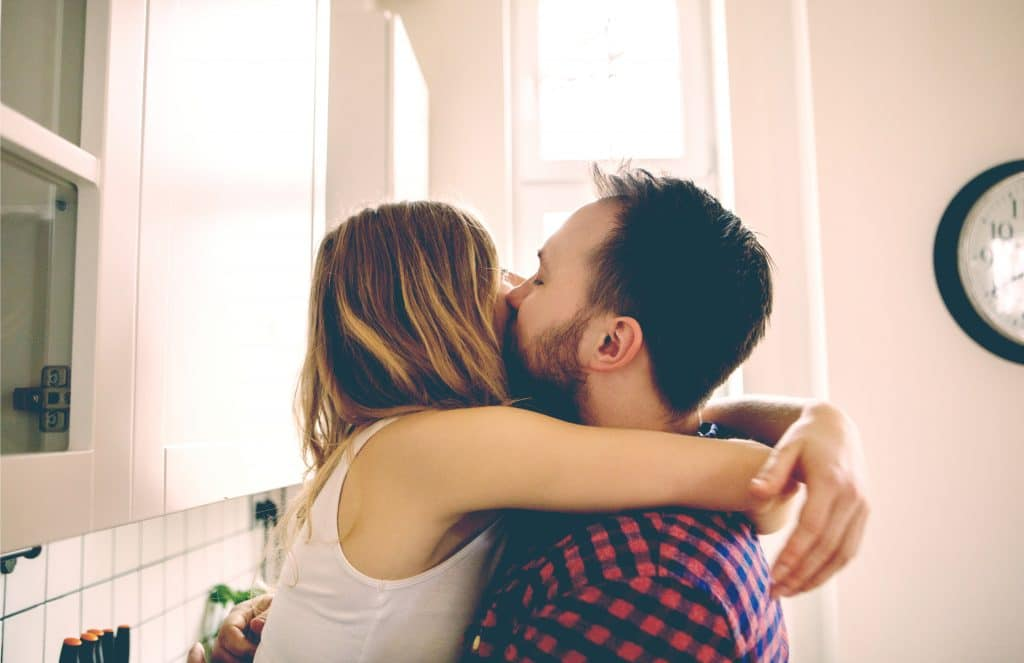 couple kiss in kitchen