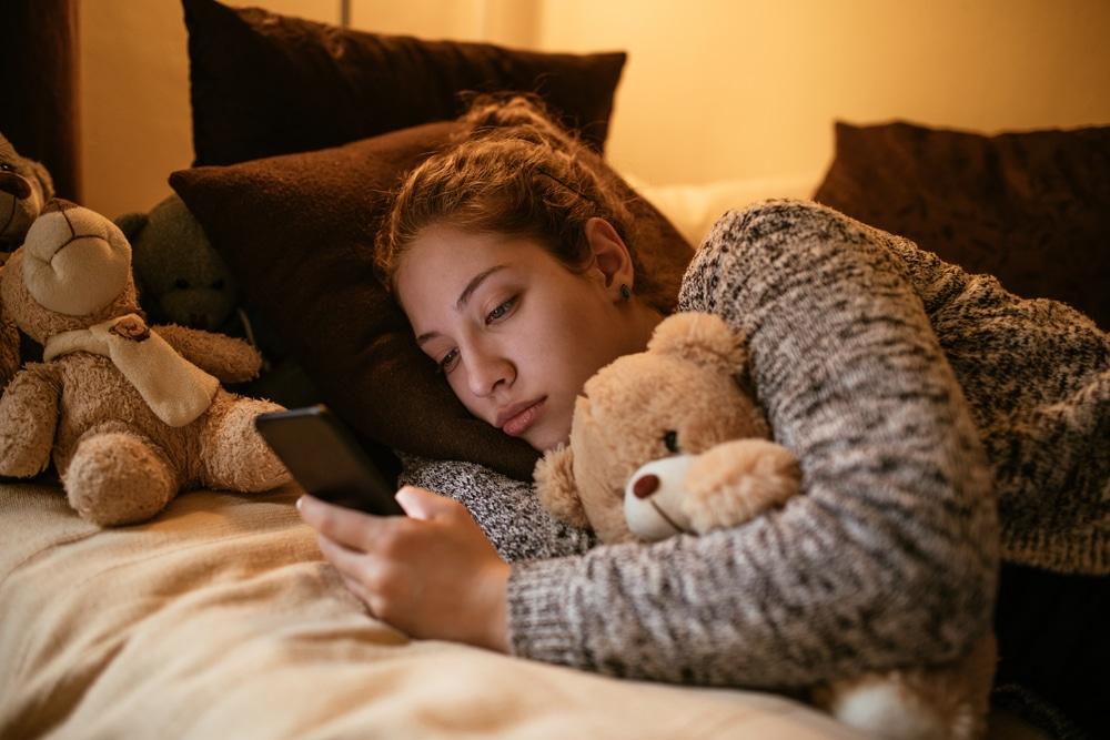 sad woman on bed with teddy bear