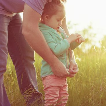 father with daughter in a field