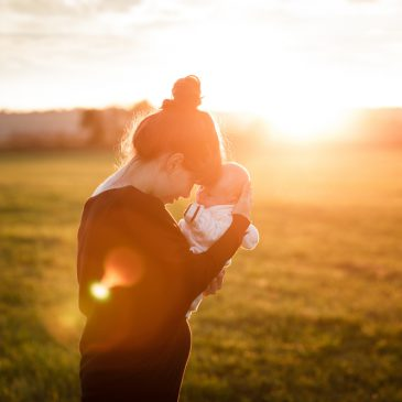 mother with newborn in a field with sun