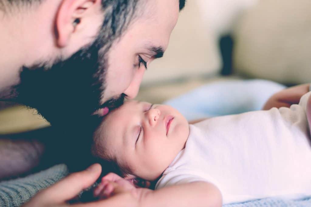 man kiss newborn's head