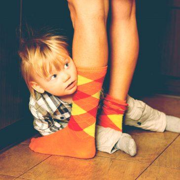 kid hide behind mom's legs