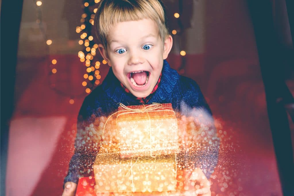 excited kid with xmas gifts
