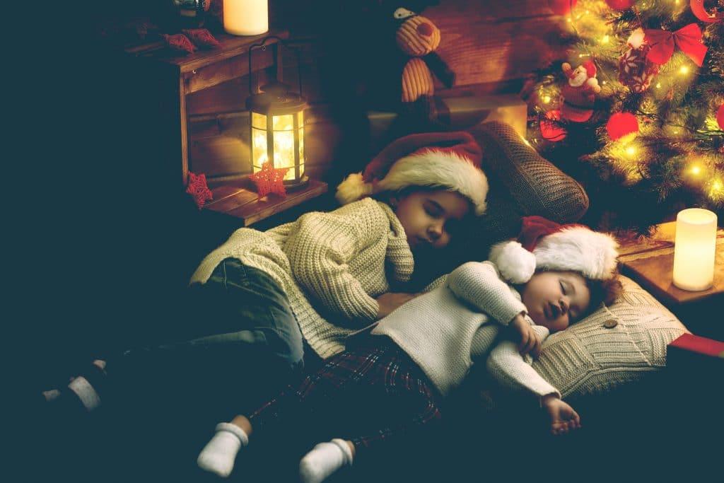 two little girls sleeping xmas tree