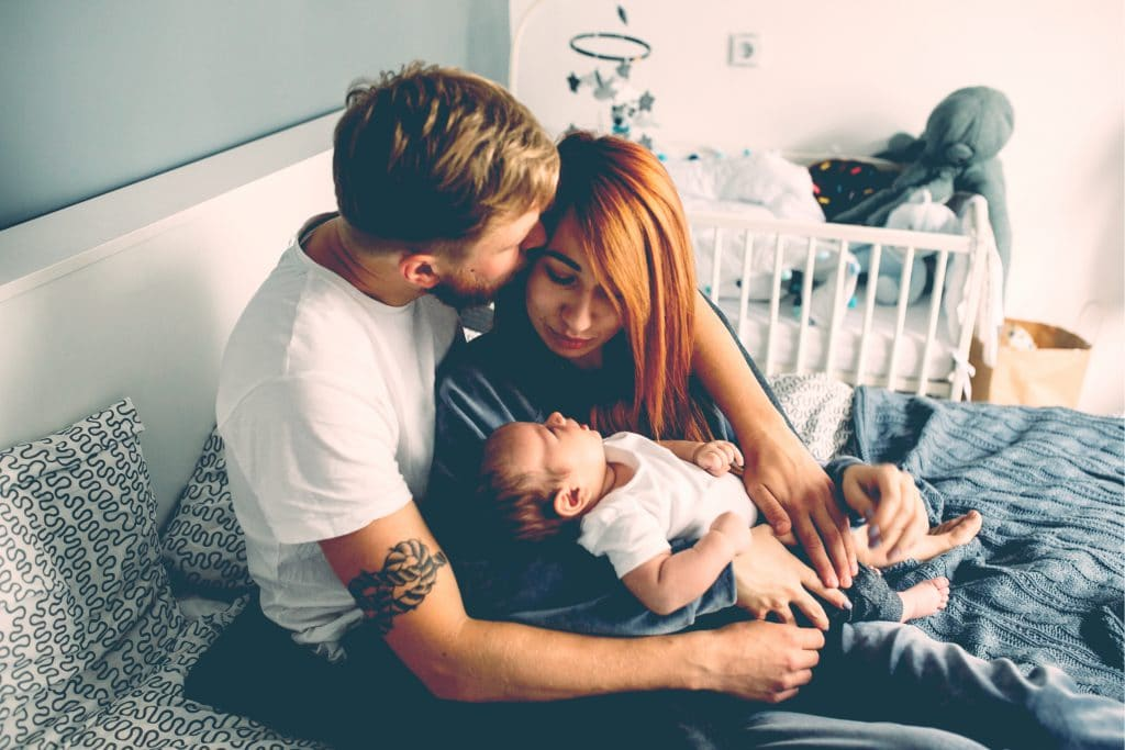 father mother and newborn in bed