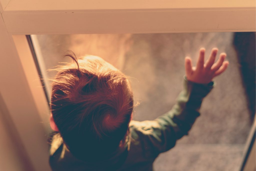 sad little boy hand on window