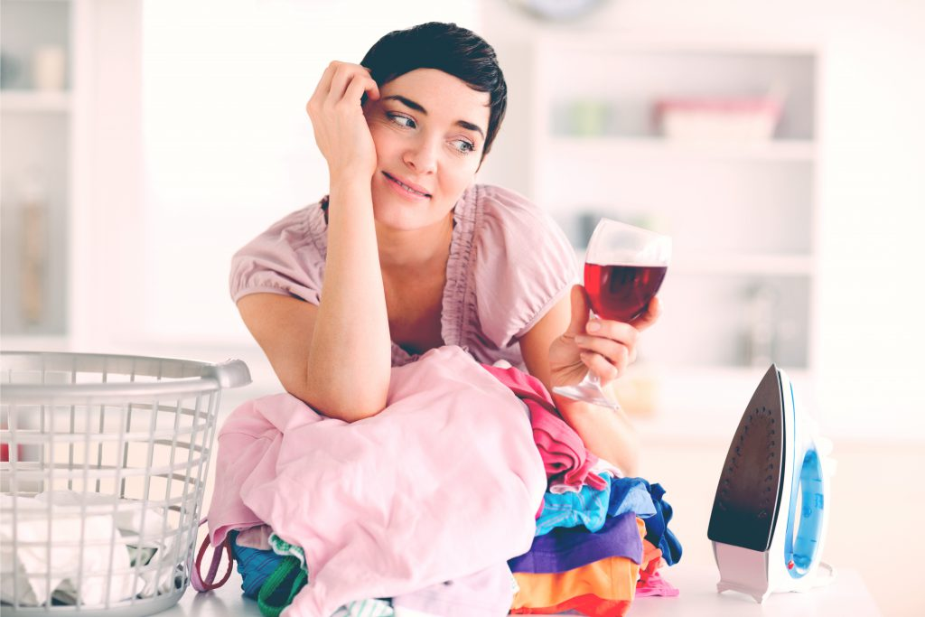 woman drinking wine with laundry