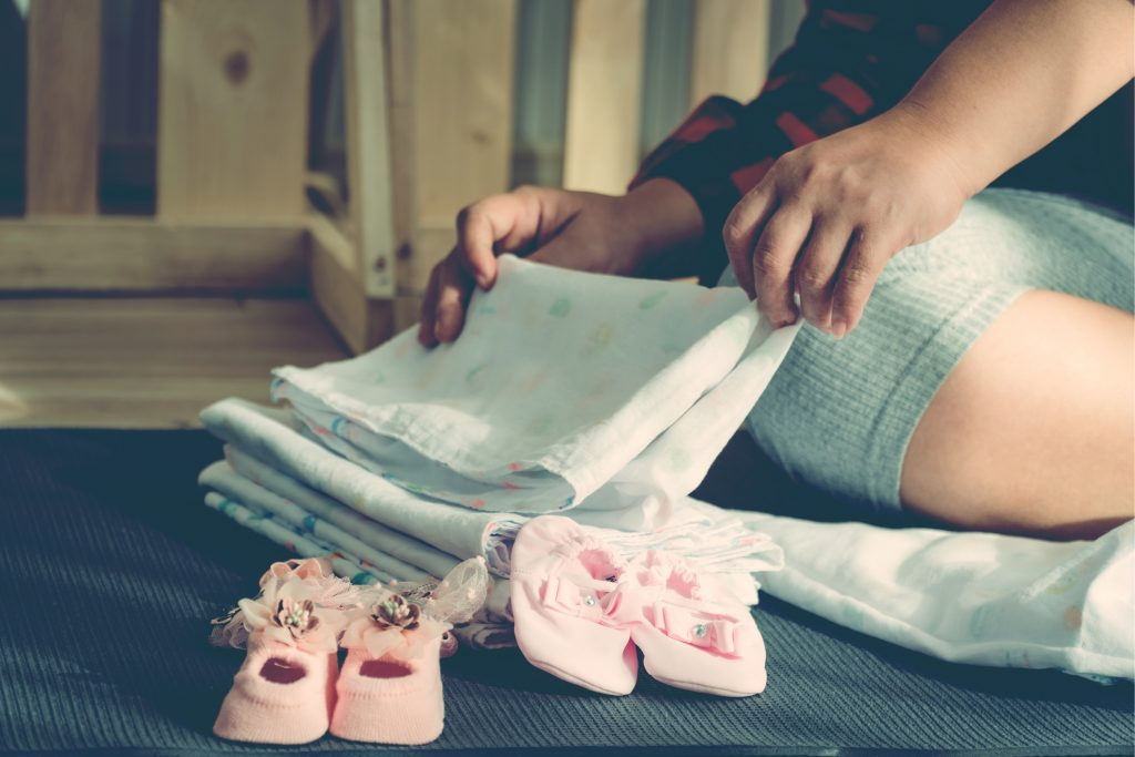 woman fold baby clothes
