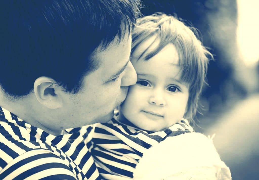 father kiss little girl