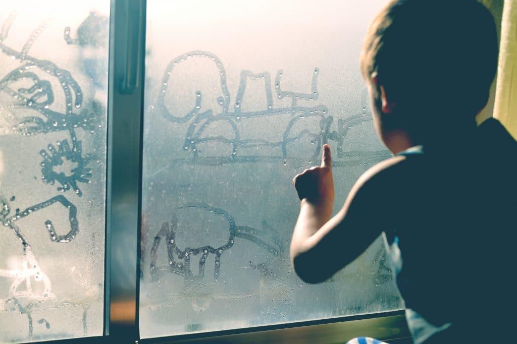 little boy in front of window