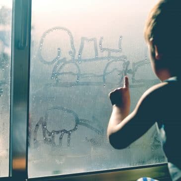 little boy in front of window