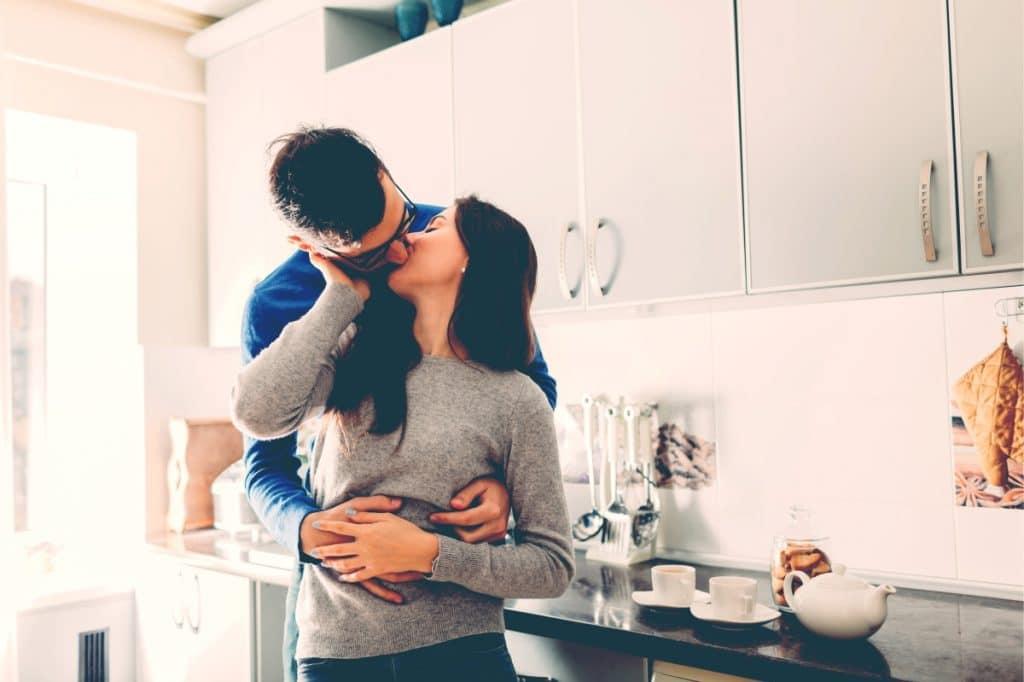 man woman kiss in kitchen